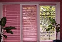 Горизонтальные жалюзи розового цвета.